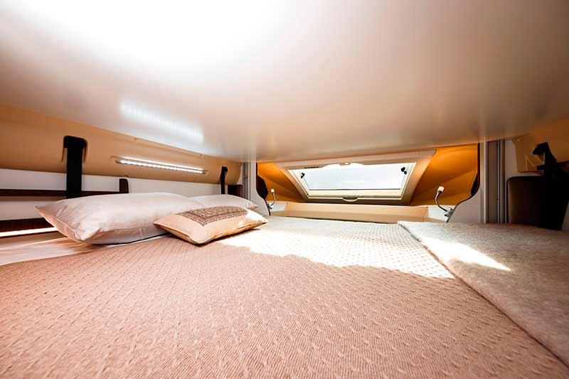 Cama superior en salón de la autocaravana
